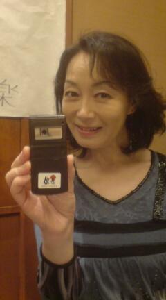 携帯を手に持って笑顔自撮りをする島田陽子
